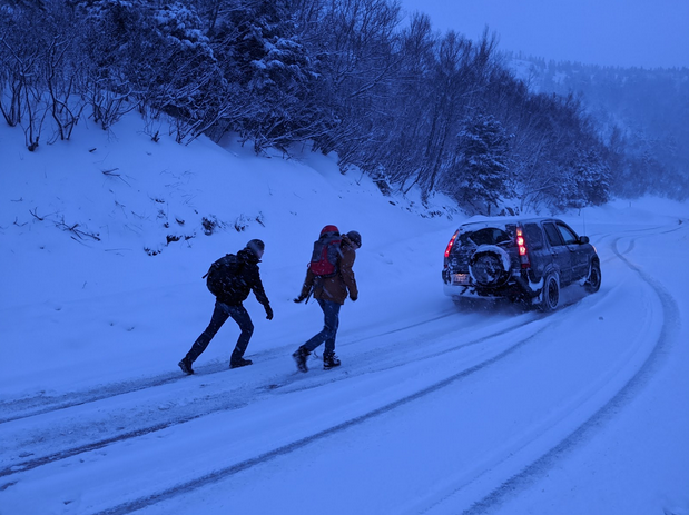 People walking in snow with car on side of road